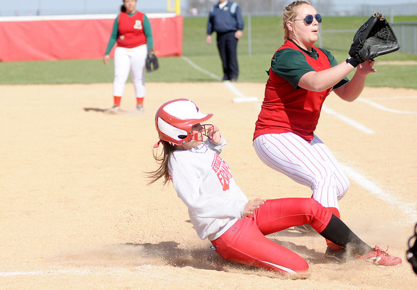 Don Knight | The Herald Bulletin<br /> Frankton's Emily Benefiel slides into home on a wild pitch as Anderson's Sydney Schmitt rushes in to cover home plate as the Eagles hosted the Indians on Wednesday.