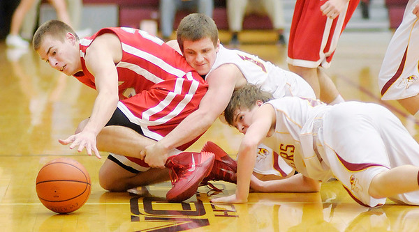 Don Knight / The Herald Bulletin<br /> From left, Frankton's Aaron Korn and Alexandria's Evan Hodges and Bryce Montgomery scramble for a loose ball as the Tigers hosted the Eagles on Friday.
