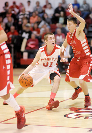 Don Knight / The Herald Bulletin<br /> Frankton's Austin Compton drives into the lane guarded by Mississinewa's AJ Grubb on Friday.