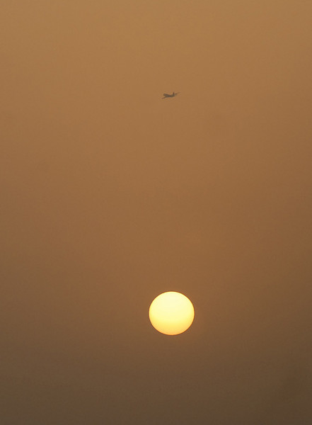 Airplane and setting sun, Dubai, U.A.E.