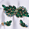 "JULIANA BROOCH AND EARRINGS<br /> <br /> Gorgeous, sparkling, graceful brooch with marquis shaped emerald green rhinestones and round AB rhinestones.  This set is in outstanding condition.  The AB stones make a sideways ""s"" through the greens, drawing your eyes to the graceful flow the the design!  The green rhinestones curve upwards at the ends yet flow like a wave from the center AB outward.  (The details are very exaggerated in these photos due to the bright sunlight..no scratches are seen under normal conditions.)  To illustrate the clarity and vivid appearance of these pieces I have photographed them in the sunlight.  The back of the brooch and clip on earrings are shiny gold.  And appear to have very slight wear that looks like finger prints in the bright light.  The design of the brooch is such that you can see through it..  The golden color behind it  in the photographs are merely a reflection of the back of the brooch.  The brooch is 3 1/2 inches long and weighs 21 grams.<br /> <br /> Matching Juliana earrings are 1 1/4 inches long and weigh 9 grams.  The clip style earrings have a large AB round stone that lays by your cheek.  Three green marquis shaped rhinestones compliment the curvature of your ear.  There is one smaller AB rhinestone at the top of the earring for balance and color.<br /> A spectacular colorful piece of vintage jewelry sure to get compliments wherever you go."