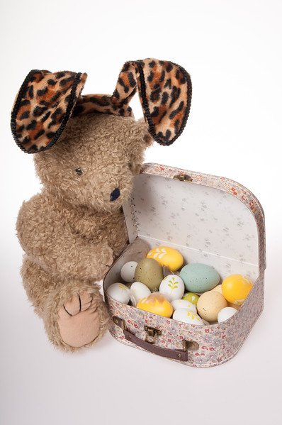 teddy bear dressed as the Easter bunny with Easter eggs  in a child's suitcase isolated on white background
