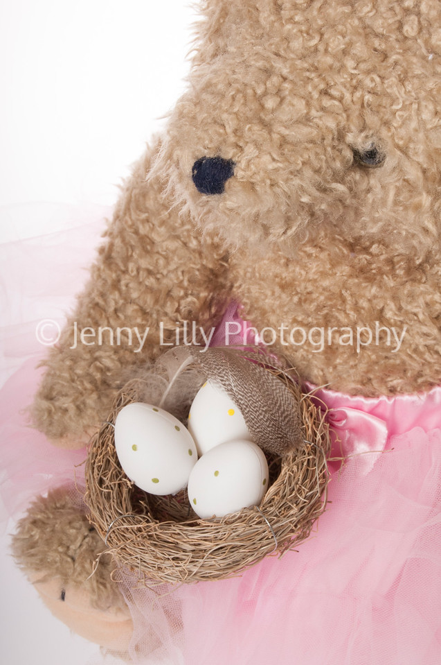 Easter teddy bear with bird's nest full of Easter eggs isolated on white background