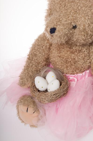 Easter teddy bear with bird's nest full of Easter eggs isolated on white background
