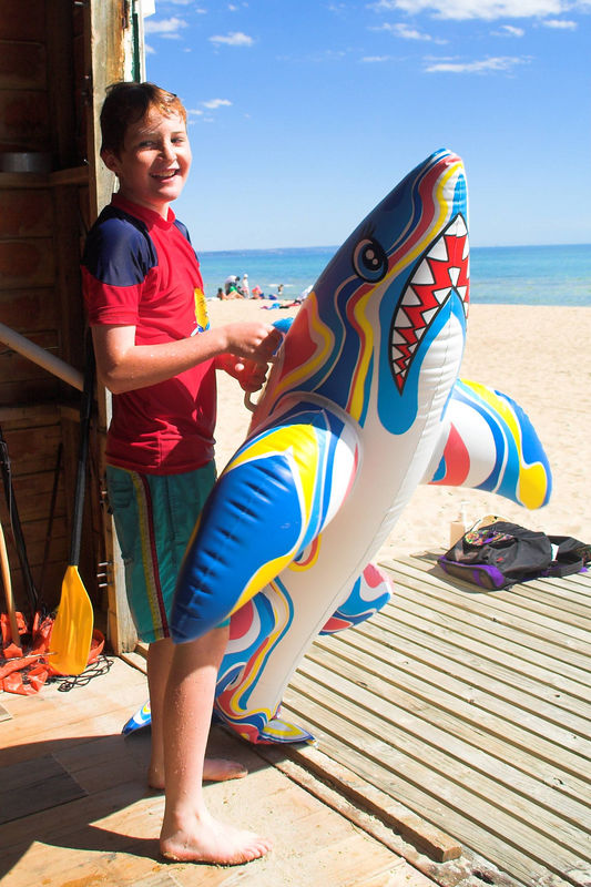 James prepares to venture into the surf: shark in hand.<br /> <br /> (Photo (c) Dennis Adami)