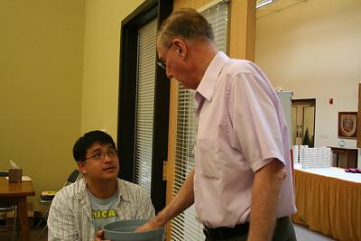 Novice Joseph Vu distributes a table number to Br. Ben Humpfer