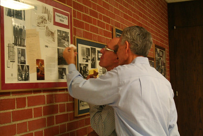 Fr. Jim Brackin and Br. Pete Mankins look at historical photos in the monastery hallway.