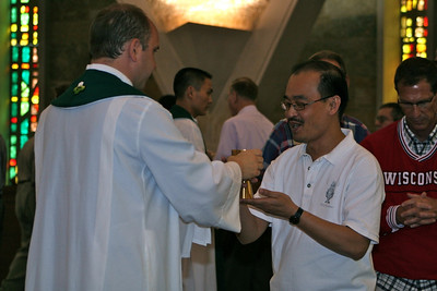 Fr. Quang Nguyen receives the cup from Fr. David Szatkowski