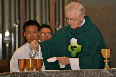 Frater Duy Nguyen and Novice Fernando Orozco look on while Fr. Mike Burke prepares for the Eucharist.