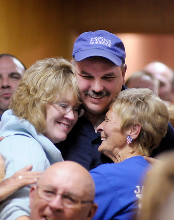 Democratic candidate for County Auditor Jane Lyons, left, hugs her husband Ray and treasurer and first deputy Patty Mauck after hearing she had won at Democratic Party Headquarters on Tuesday.