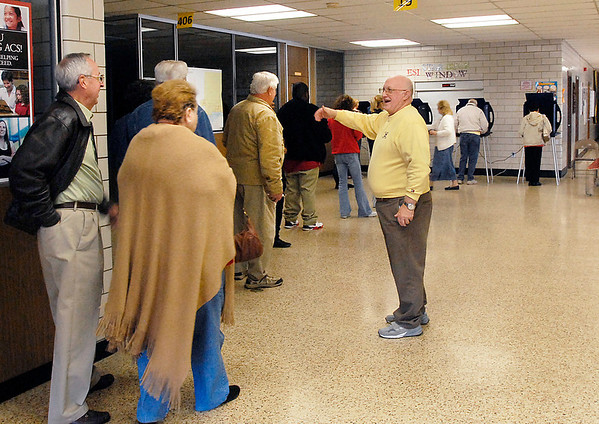 Ward 1, precinct 7 poll inspector Doug Waltermire directs the line of waiting voters to move up to make room for more voters coming in the voting site.