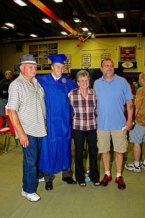 Austin Dauenhauer poses for pictures with family members following his graduation from Elwood High School.