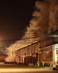 Smoke billows from the rear end and roof of Elyria foundry. photo by Ray Riedel