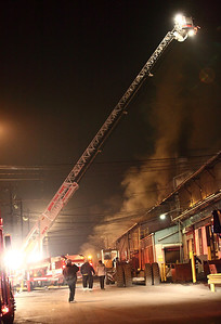 Avon fire department ladder truck surveys the roof of the burning foundry. photo by Ray Riedel