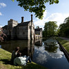 Visitors looking across the moat to Baddesley Clinton, Warwickshire.