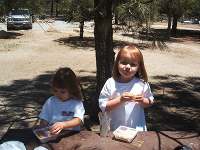 Mia and Payton eating lunch at a campsite next to a small lake.