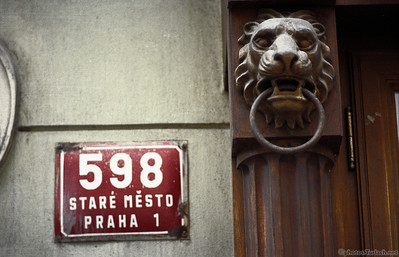 a Lion Head and a sign on an old building in Prague.