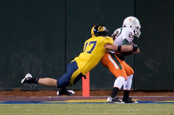 27 December 2008:  Miami Hurricanes wide receiver Thearon Collier (28) scores a touchdown as California Golden Bears cornerback Chris Conte (17) makes the tackle during the second half of the Golden Bears' 24-17 victory over the Hurricanes in 2008 Emerald Bowl at AT&T Park in San Francisco, California.