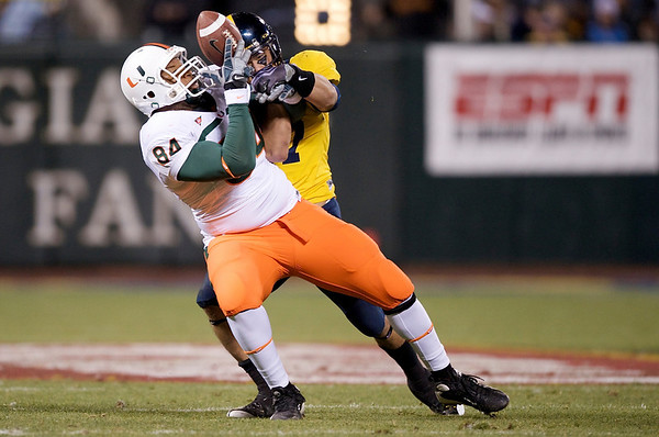 27 December 2008:  Miami Hurricanes tight end Richard Gordon (84) makes a first down catch in front of California Golden Bears linebacker Anthony Felder (7) during the first half of the 2008 Emerald Bowl between the Golden Bears and the Hurricanes at AT&T Park in San Francisco, California.  The Golden Bears prevailed 24-17 over the Hurricanes.
