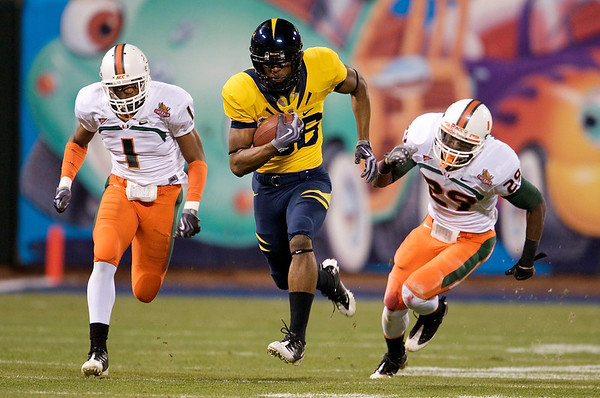 27 December 2008:  California Golden Bears wide receiver Verran Tucker (86) heads up field past Miami Hurricanes linebacker Brandon Harris (1) and safety Jojo Nicolas (29) for a long gain during the first half of the 2008 Emerald Bowl between the Golden Bears and the Hurricanes at AT&T Park in San Francisco, California.  The Golden Bears prevailed 24-17 over the Hurricanes.