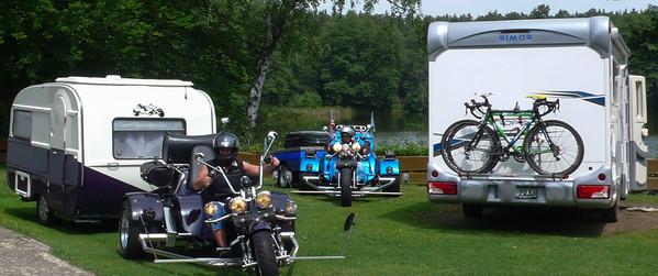 Zwei höchst unterschiedliche Fortbewegungsmittel: Trikes mit Wohnwagen und Wohnmobil mit Ironman-Trainingsbikes. Typische Mischung für die Idylle am See.