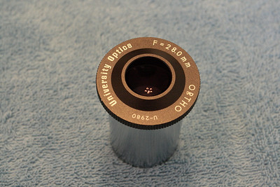 "Long discontinued 28mm Orthoscopic eyepiece from perhaps late 1970's vintage. Might be even earlier as the eyepiece has a serial number U-2980. It is also described as a ""flat top eyepiece"", even though the cap in this picture clearly shows a semi volcano shape to it."