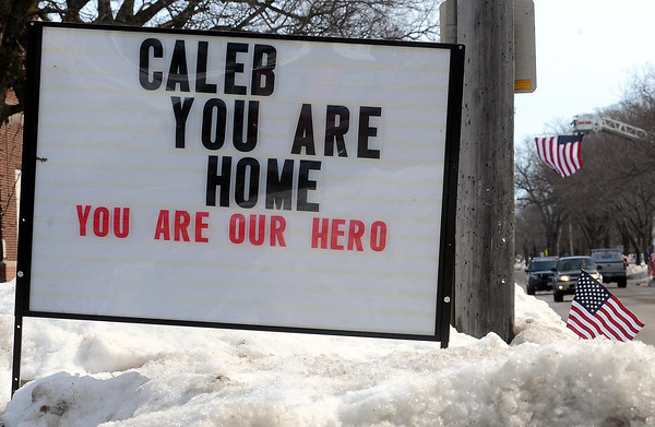 John Cross<br /> A sign along the funeral procession route welcomes fallen Marine Caleb Erickson home.
