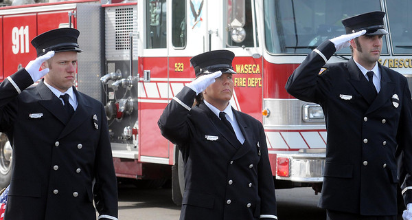 John Cross<br /> Members of the Waseca Fire Department stand at attention and salute the passing funeral procession carrying fallen Marine Caleb Erickson to the Woodville Cemetery in Waseca on Monday.
