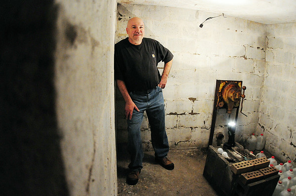 Ed Enos of Ellwood City stands in his 9-by-12-foot fallout shelter. The shelter was built in 1961 by the former owner of Enos' home, Robert Forsyth. On the wall at right is a hand-cranked pump that would be used to draw air into the shelter through a pipe in the garage above. Further to the right are some of the nearly 50 one-gallon jugs of water that Enos found in the shelter when he first entered it in 1997. — Tiffany Wolfe/NEWS