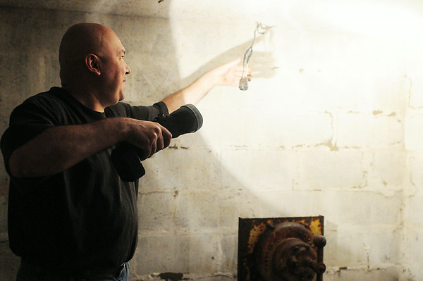 Ed Enos examines electrical wiring that leads into the shelter. — Tiffany Wolfe