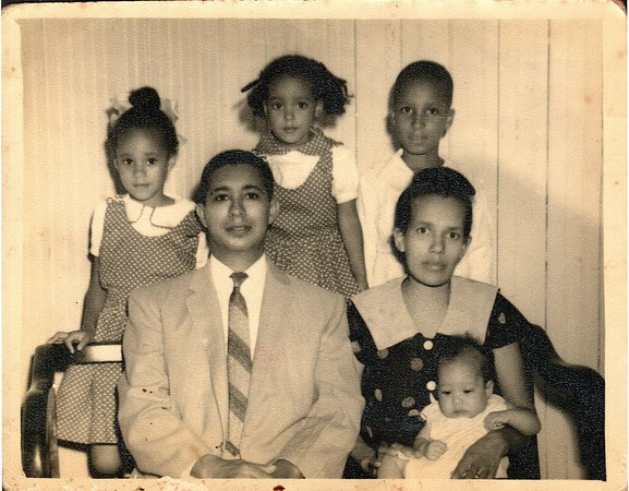 Family portrait of my mother, her two sisters, brother and parents. Mami is standing in the middle. My grandparents had six children, two more would follow this picture.