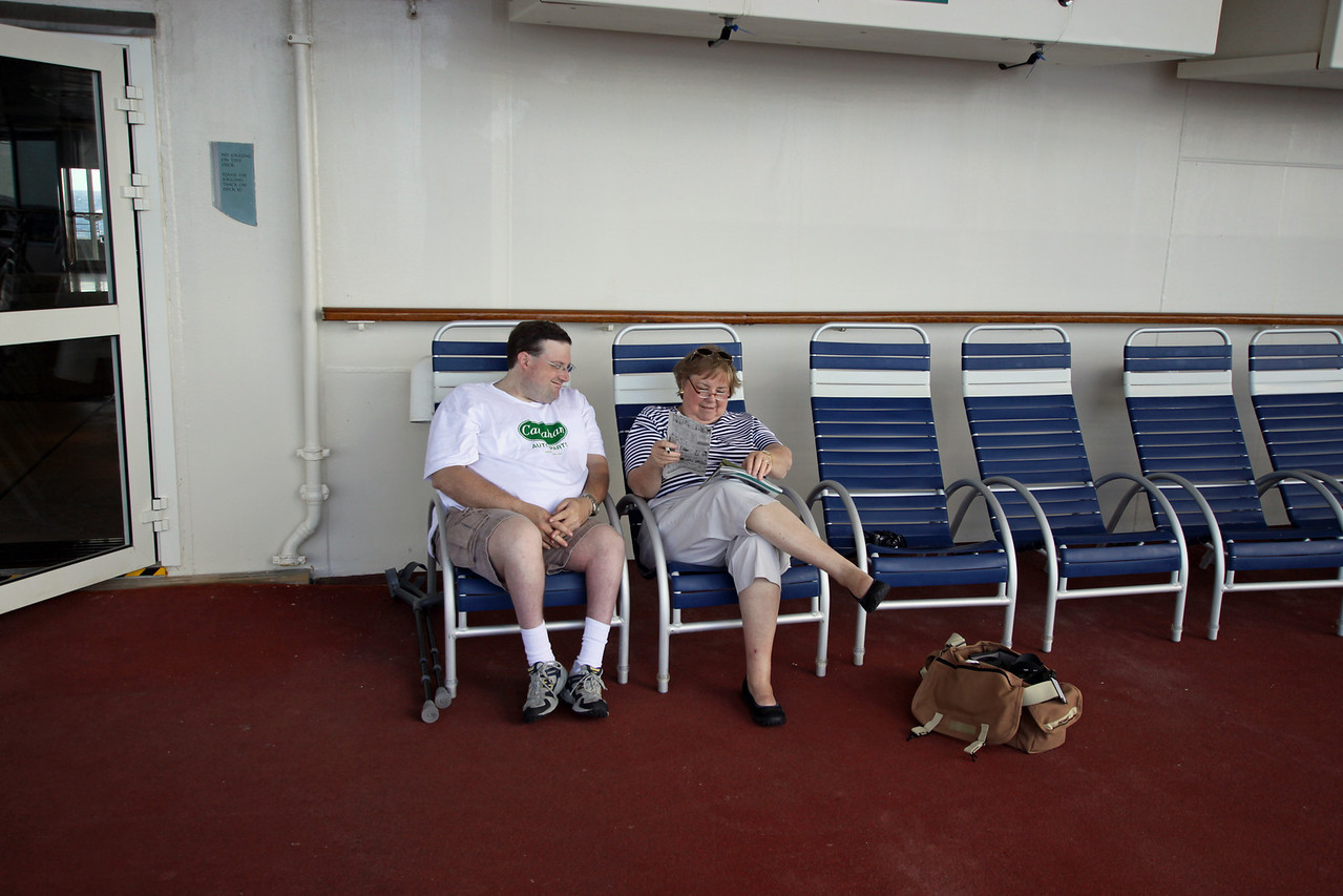 Relaxing on Deck 5 of the Enchantment of the Seas.  My presence noted through my camera bag on the deck.
