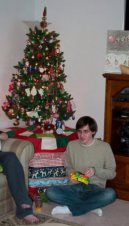 Derek opening his presents next to Mom and Dad's Christmas tree.