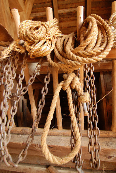 ropes and chains hanging and ready for use in a barn