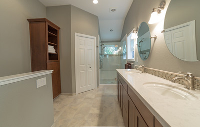 Petersen Master Bath Eight weeks later:  10' ceilings, heated tile floors, walk-in closet, dual vanity with Silestone counters, undermount sinks and glass mosiac tile splash, Toto one piece toilet.  Cherry cabinets with tall storage cabinet with glass doors.  Heavy glass pivot door with tile shower, including bench, personal spray, new window and nickel safety bars.