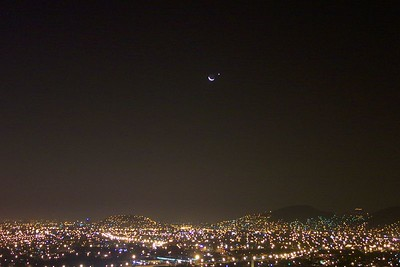 May 2002 Lima, Peru - This is the crecent moon with Jupiter over Lima's skyline. There is something special about this picture, I'm not really sure what it is but I don't get the same feeling with any other picture that I have. I think a big part of it is the fact that I know everything came out as well as it possibly could have. The camera worked as perfectly as it could have, the exposure was perfect, the city lights are not over exposed, their distinct colors are clear, the camera caught the light reflected off of the haze over the city, and fact that satisfies me the most - you can actually see the sunlight reflected off of the Earth, then off of the moon, and back to earth which is why you can see a faint but complete circle of the moon. On top of all that, I managed to take this picture in uncompressed .TIF format which means the original is as prestine as can be, which also means the original picture is 9MB in size. The reason that makes the situation more difficult is first, it took at least 30 seconds for the image to be written to the flash card in the camera, delaying a potential re-take of a scene that changes every minute. The other variable is images that size take up a lot of space, so if you don't get it right within the first few tries, your 64MB flash card fills up (the size card I had at the time), and then you need to go back and delete the misses to make room for your next attempts. A further delay that could result in missing the shot you hoped for.  By the way, if you wanna see something neat, try this..  Go to http://space.jpl.nasa.gov/  Then select the following: SHOW ME: ...The Moon   AS SEEN: From Earth May 16, 2002 11:50 UTC I WANT A FIELD OF VIEW OF: 30 degrees Then click on the Run Simulator button on the bottom left. The simulator is imperfect, the real date was the 15th of May but the simulator shows a more accurate picture a day later.