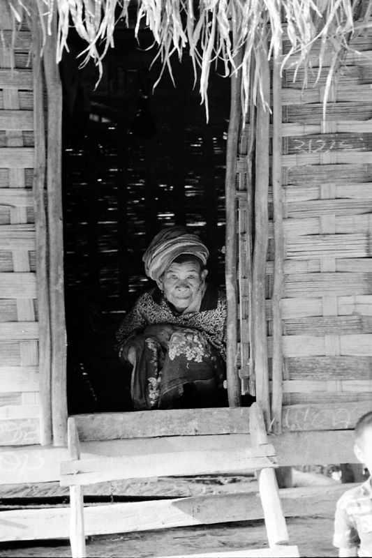 laos -old lady crouching in doorway 2