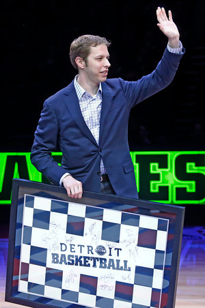 NASCAR driver Brad Keselowski waves to the crowd after receiving a plaque signed by the Detroit Pistons in honor of his 2012 NASCAR Sprint Cup Series championship during halftime of an NBA basketball game against the Millwaukee Bucks Tuesday, Jan. 29, 2013, in Auburn Hills, Mich. Keselowski lives in neighboring Rochester Hills, Mich. (AP Photo/Duane Burleson)