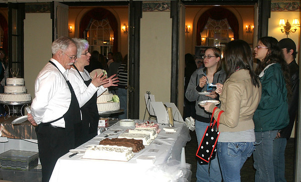 Ben Morris and Barbara Morris of the Village Cup and Cakes display booth talk about the wedding cakes baked right in the kitchen of the Keosauqua shop. They were at the BLANK SHOW Sunday.<br /> Mark Newman/The Courier