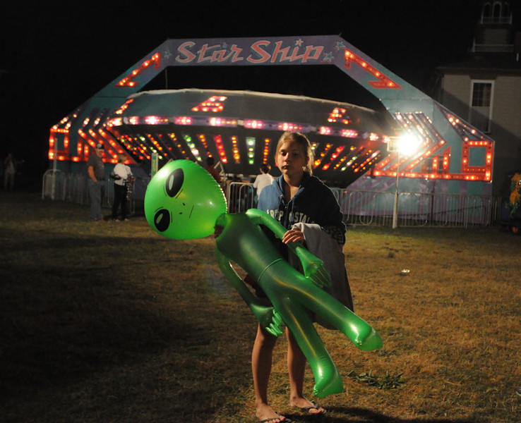 Young girl at carnival holding blow up alien in Bristol RI, July 2010.