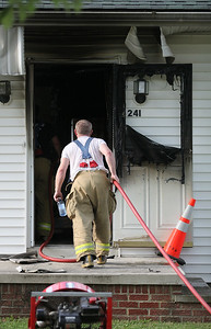 A fire fighter helps douse hot spots after a fire that broke out at a house at 241 Forest Street in LaGrange around 4:45 P.M. Monday. photo by Ray Riedel