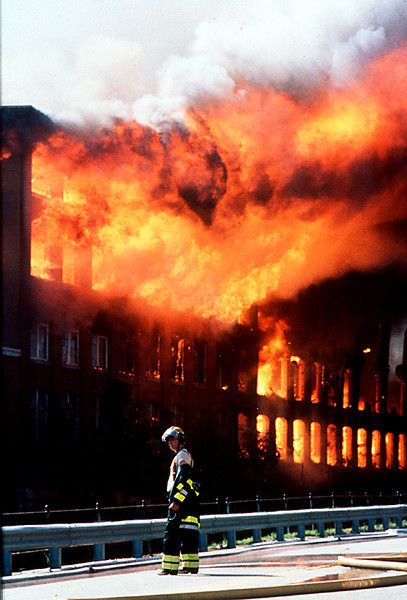 A firefighter is helpless in stopping the inferno that started at one end of the Worumbo Mill in Lisbon Falls several hours earlier.