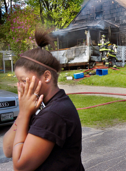 Deanna Morency looks away as Auburn firefighters enter her home on Carlton Road. Firefighters quickly knocked down the flames soon after they arrived, but the porch was destroyed and the interior heavily damaged.