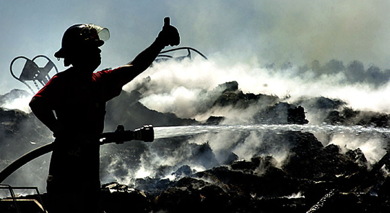 A firefighter signals for more pressure while hosing down hot spots after an early morning fire in Auburn destroyed a barn and house at Graceland Dairy Farms on the Penley Corner Road in Auburn