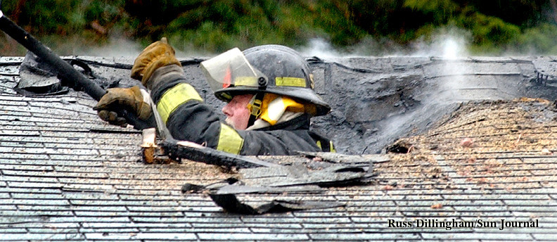 Auburn firefighter Douglas Wiles breaks through the roof as he tackles the smoldering remains of a fire on Kyle Lane in Auburn