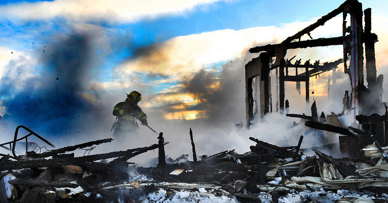 A Turner firefighter looks for hot spots in what remains of a house on Clover Lane in Turner.  When firefighters arrived, smoke was pouring out of nearly every window in the house.