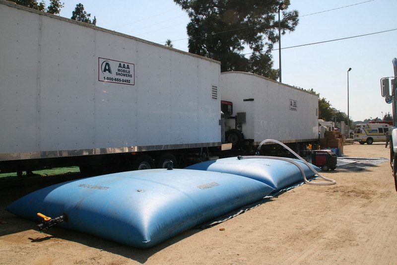 "Blue bags are the refillable clean water source for the showers & laundry. The flat gray one behind the generator is for the used ""gray water"". Tanker trucks continually add clean water and take away the gray water."