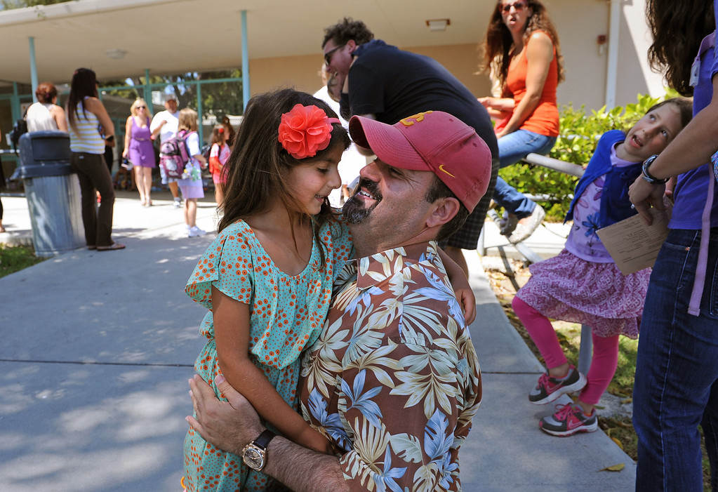 . Tom Meneshian greets his daughter Sophia after the first day of first grade. Students at South Shores Performing Arts Magnet School in San Pedro leave school on the first day of classes.   Photo by Brad Graverson 8-13-13