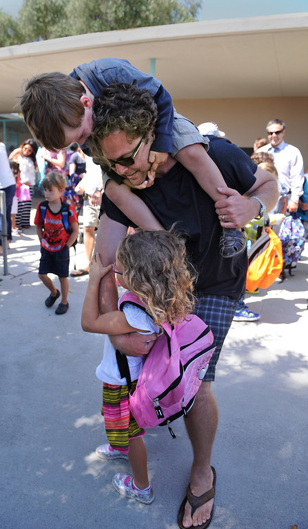 . Gregory Hildebrand has his hands full picking up his daughter Gwendolyn (1st grade) as son Kennedy goes along for a ride. Students at South Shores Performing Arts Magnet School in San Pedro leave school on the first day of classes.   Photo by Brad Graverson 8-13-13