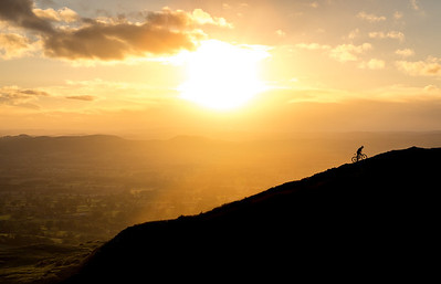 Self Portrait: Climbing Clee Hill The sun sets over the Welsh Mountains creating a beautiful silhouette of Clee Hill